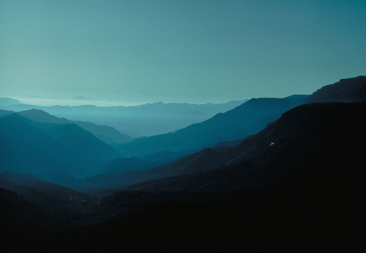 The closest hills are simply black shadows, while those farther away are cast in the blue light of distant fog at sunset.